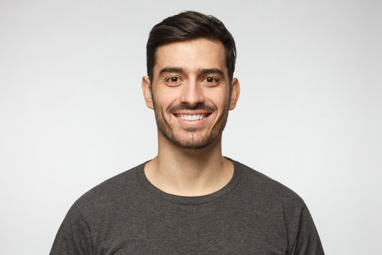Close-up portrait of smiling handsome young man in casual t-shirt, isolated on gray background
