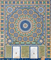 Traditional ornamental drinking fountain in medina in Meknes, Morocco. Decorated fountain with mosaic tiles. Ornate mosaic and traditional Islamic religious art. Ancient oriental Moroccan