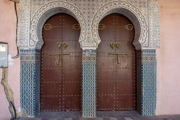 Traditional Moroccan style design of an ancient wooden entry door. In the old Medina. Typical, old, brown intricately carved, studded, Moroccan riad door in Meknes, Morocco.