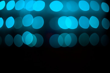 Abstract glitter defocused blue lights bokeh texture on black background