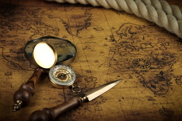 Vintage Compass and magnifying glass lies on an ancient world map - adventure stories background