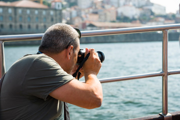 A man from a boat taking pictures of the cityscape of Porto. Selective focus.