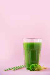 Glass of green celery smoothie on pink background. Banner with copy space. Fresh juice for detox....