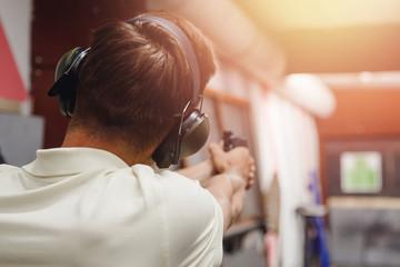 Shooting range gun. Man shoots pistol in noise protection headphones
