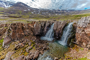 Waterfall and mountain landscape in Fjardabyggd municipality in Eastern Iceland