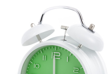 Cropped twin bells analogue alarm clock with green clock face shows completed hour, concept on white background