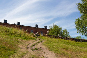 Old granite fortifications and old guns of the historic fort Suomenlinna Sveaborg in Finland on a summer day.