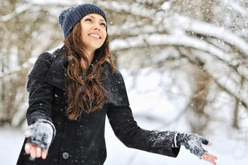 Beautiful girl playing with snow in winter park