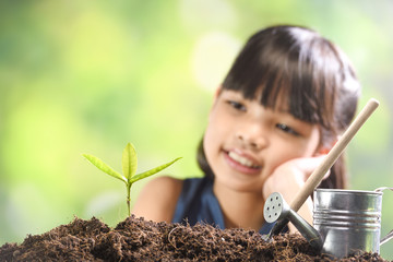 A girl planting young plant on soil with a hope of good environment