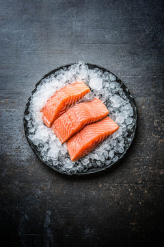 Portioned raw salmon fillets in ice on plate - Top of view
