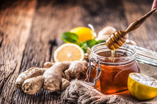 Honey jar dipper ginger lemon and mint herbs on wooden table