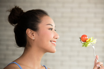 Asian woman in joyful postures with hand holding salad on fork