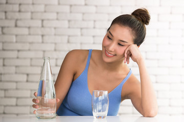 Asian woman in joyful postures with bottle and glass of drinking water on the side