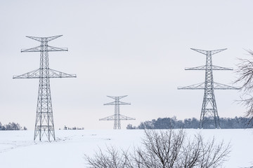 Construction of high voltage pylons in winter. Assembled power transmission line supports, ready for installation.