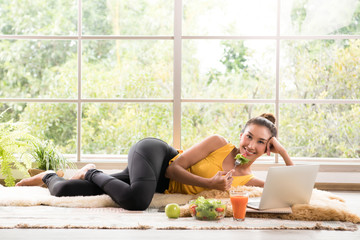Healthy Asian woman lying on the floor eating salad and looking at camera