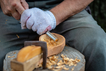 Craftsman demonstrates the process of making wooden spoons handmade using tools. National crafts concept.