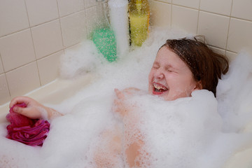 Little baby girl having soapy bath at home