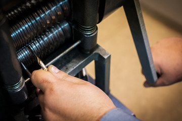 Jeweler forming a piece silver or gold in roll press