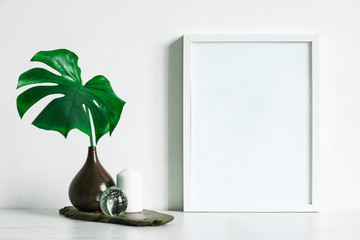 Minimalistic composition of mock up photo frame with green tropical leafs in brown design vase on the wooden piece. Stylish concept of mockup frame. White backgrounds wall.