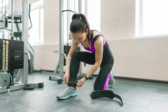 Young smiling woman wearing leather ankle straps prepares to exercise on fitness machine in the gym. Fitness, sport, training, people concept