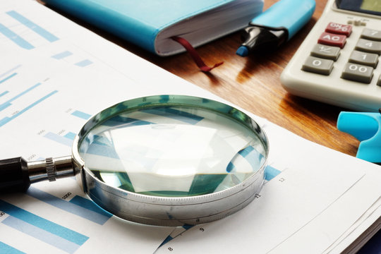 Business audit. Magnifying glass on financial documents.