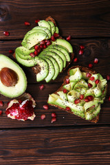 sliced avocado and ripe pomegranates on toast bread with spices and avocado.