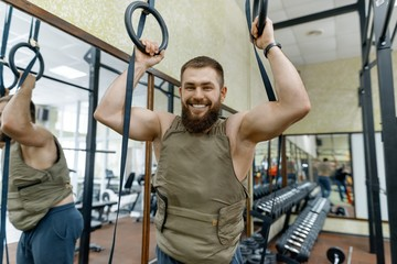 Portrait muscular caucasian bearded man dressed in weighted vest in the gym, military style
