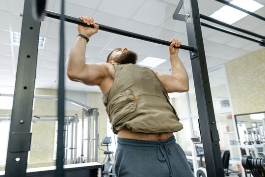 Military sport, muscular caucasian bearded adult man doing exercises in the gym dressed in bulletproof armored vest
