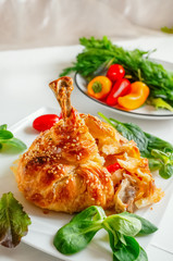 Chicken legs in dough with vegetables and lettuce.