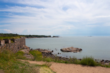 Coast, stones, old wall and view from Suomenlinna island to the Gulf of Finland and islands in it on a summer day in Finland.