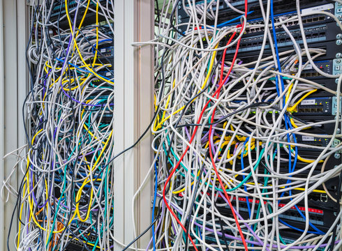 Switchboard panel with chaotic mess  cables connections, Chaos In Server Room, The tangled network cable