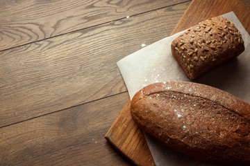Creative background, freshly baked sliced rye bread on a wooden cutting board, flat lay, copy space. The concept of fresh pastry, black bread.