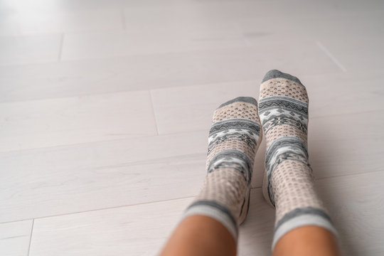 Winter socks woman wearing wool socks at home on hardwood floor. Warm heat inside apartment concept, floor heating feet closeup.