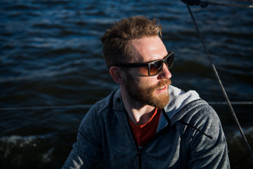 Close up portrait Bearded man model wearing sunglasses and hoodie looks away, sunset in the sea scenery.
