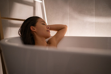 Luxury bath woman relaxing in hotel spa bathtub or home bathroom for total relaxation. Asian lady taking a bath sleeping in warm water, winter wellness.