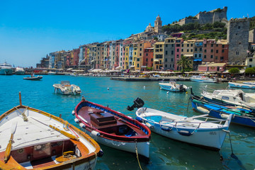 In de dag Blauwe jeans Portovenere, Italy. view of the fishing village of Portovenere from the marina. In the foreground small fishing boats. In the background colorful houses dominated by the walls of the Doria