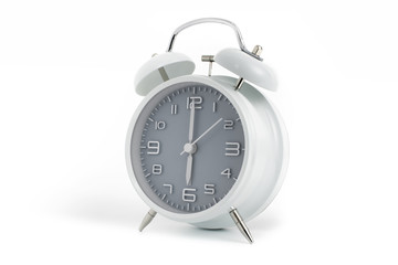 Twin bells analogue alarm clock with gray clock face shows six o'clock, 6 AM PM; concept on white background