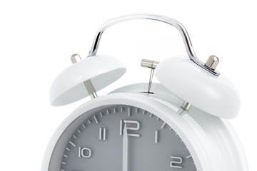 Cropped twin bells analogue alarm clock with grey clock face shows completed hour, concept on white background
