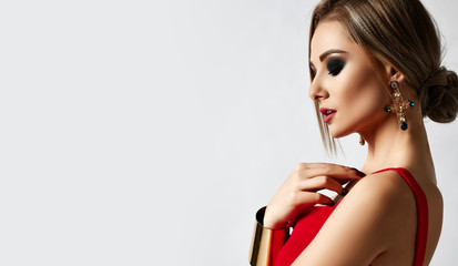 Young sensual beautiful woman posing in fashion red dress and big gold bracelet on gray