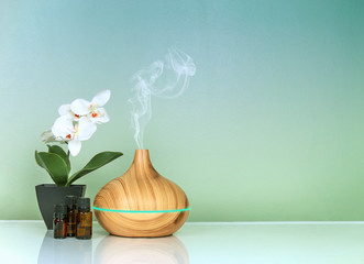 Electric Essential oils Aroma diffuser, oil bottles and flowers on green blue gradient surface with reflection
