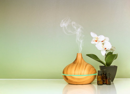 Electric Essential oils Aroma diffuser, oil bottles and flowers on green gradient surface with reflection
