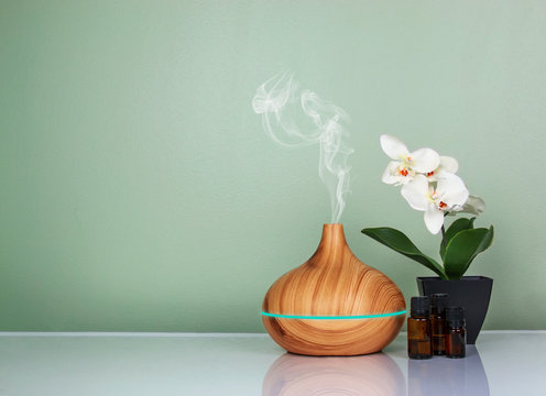 Electric Essential oils Aroma diffuser, oil bottles and flowers on light green surface with reflection