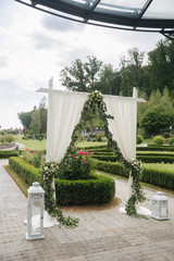 Weddind decoration on open air. Floral decor of a beautiful white arch. Beautiful beckground view of trees