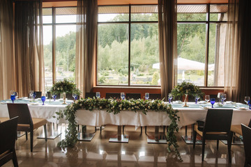 Decorated table for wedding celebration. Bright restaurand with a lot of windows