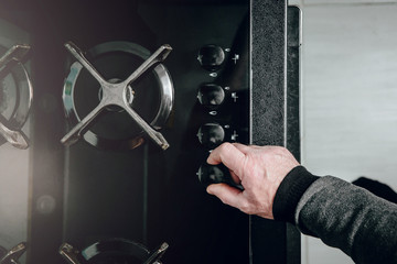Top View of a man unscrewing a gas cock. Using a gas oven to prepare dishes. The man fires the gas to start cooking.