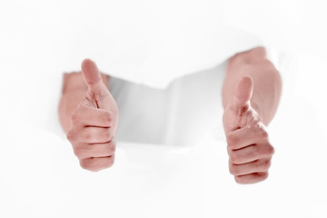 man breaking through the paper wall and showing thumbs up.