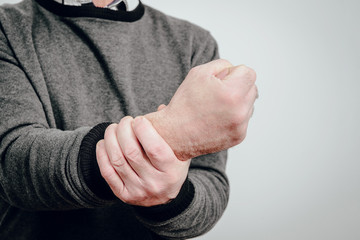 Pain in the wrist. The man is holding his hand, he feels strong pain. Medical and pharmaceutical concept, feeling of pain, suffering. An attempt to heal, cure. Health problems of people in the world.
