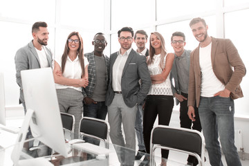multinational business team standing in a bright office