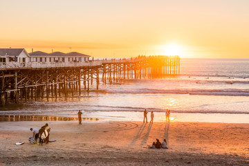 People doing activities at the beach near the pier with beautiful sunset. Pacific Beach in San Diego, California Wall mural