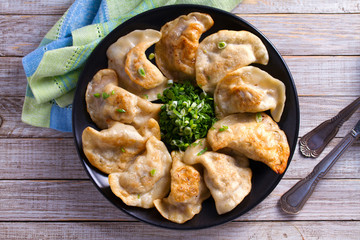 Fried dumplings stuffed with meat and served with chopped parsley and spring onion on a black plate on a wooden rustic table. View from above, top studio shot